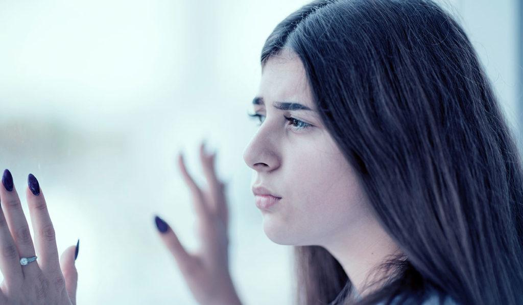 Frau schaut aus Fenster mit Händen am Glas