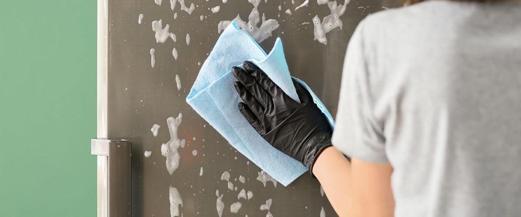 Frau reinigt Glastür mit Tuch