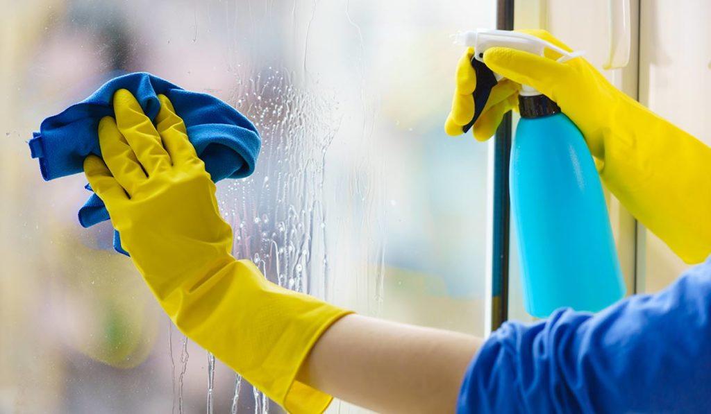 Frau reinigt Fenster mit Folierung.