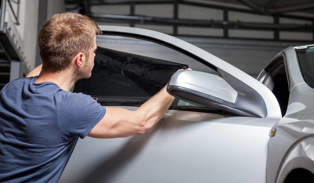 Mann bringt getönte Folie an Autofenster an.