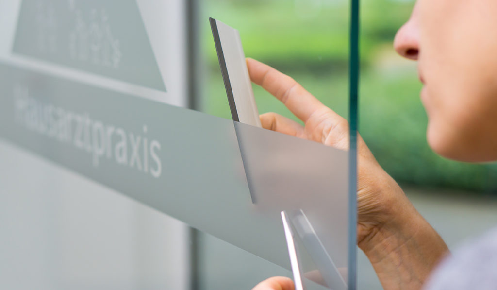 Frau bringt Beschriftung an die Glastür einer Praxis an.
