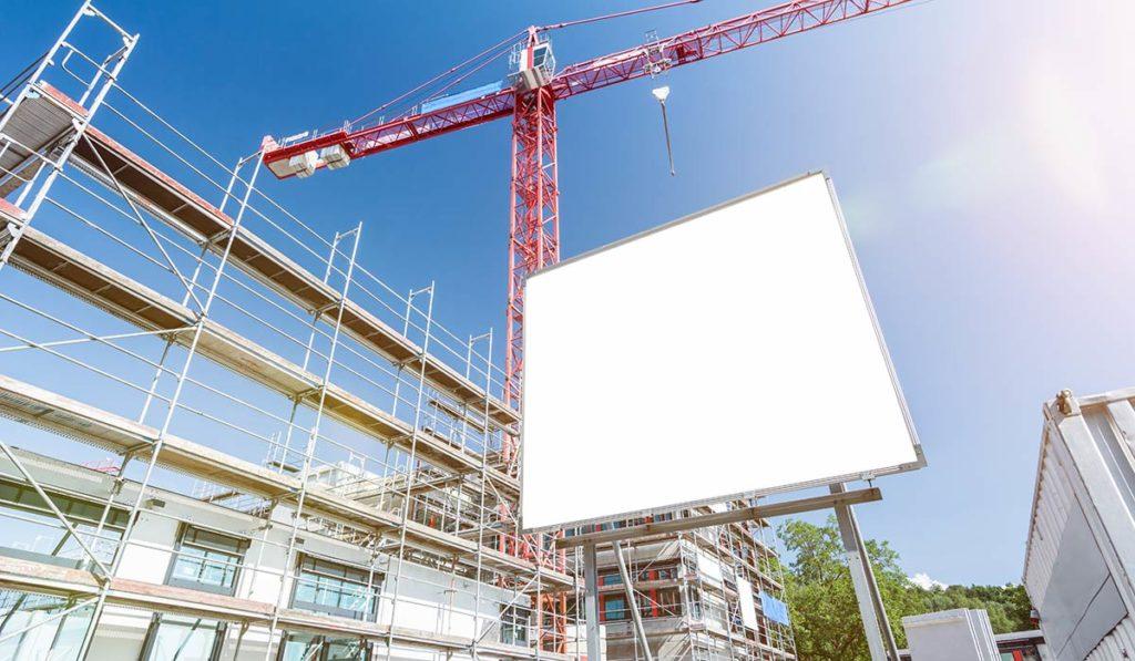 Bauschild als Werbefläche vor einem Kran.