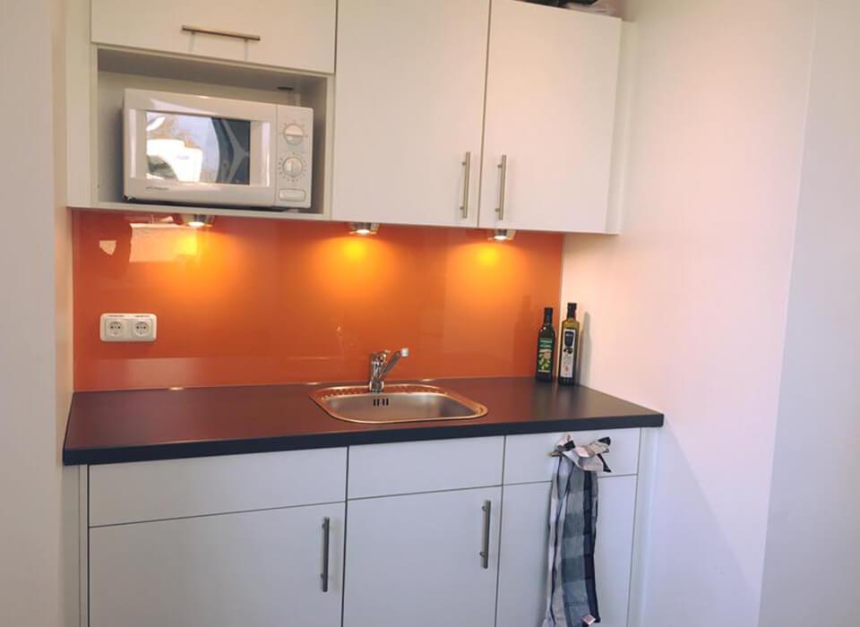 Glasrückwand in orange metallic