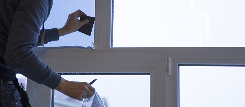 Mitarbeiter von A-Z Glaserei & Folientechnik GmbH aus Berlin bringt Sonnenschutzfolie an Fenster an